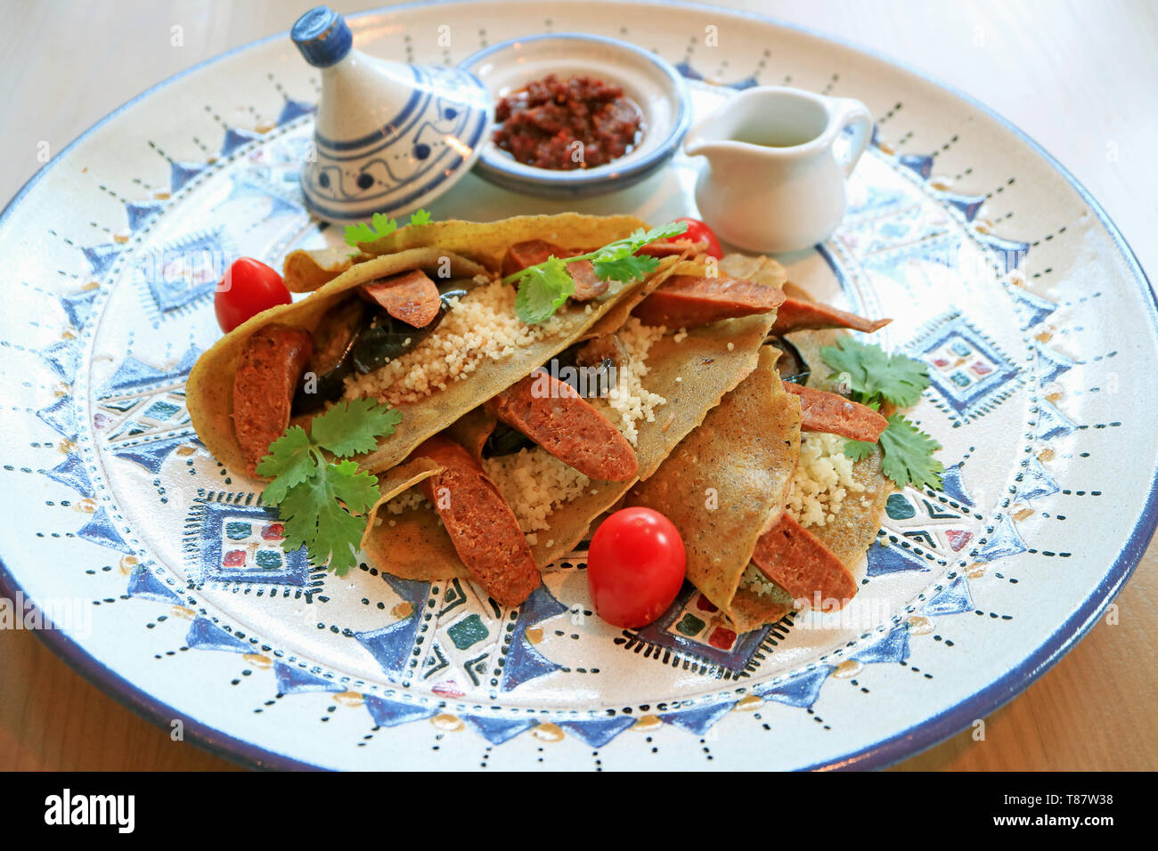 Delectable Moroccan Style Savory Crepes with Couscous, Moroccan Sausages and Eggplants - Stock Image