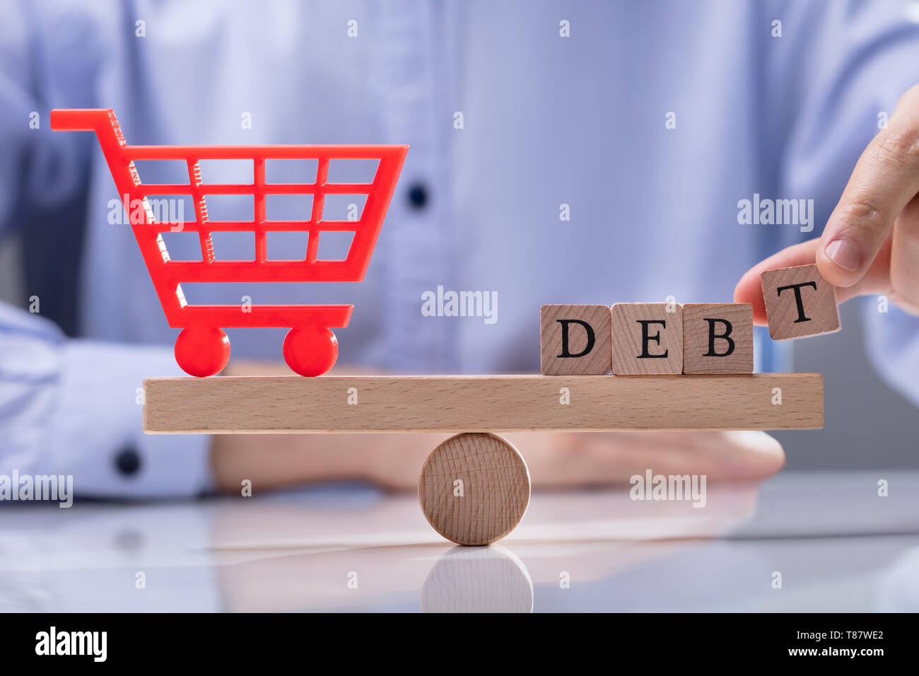 Person's Hand Putting Word Debt On Seesaw To Balancing Red Shopping Cart Icon - Stock Image