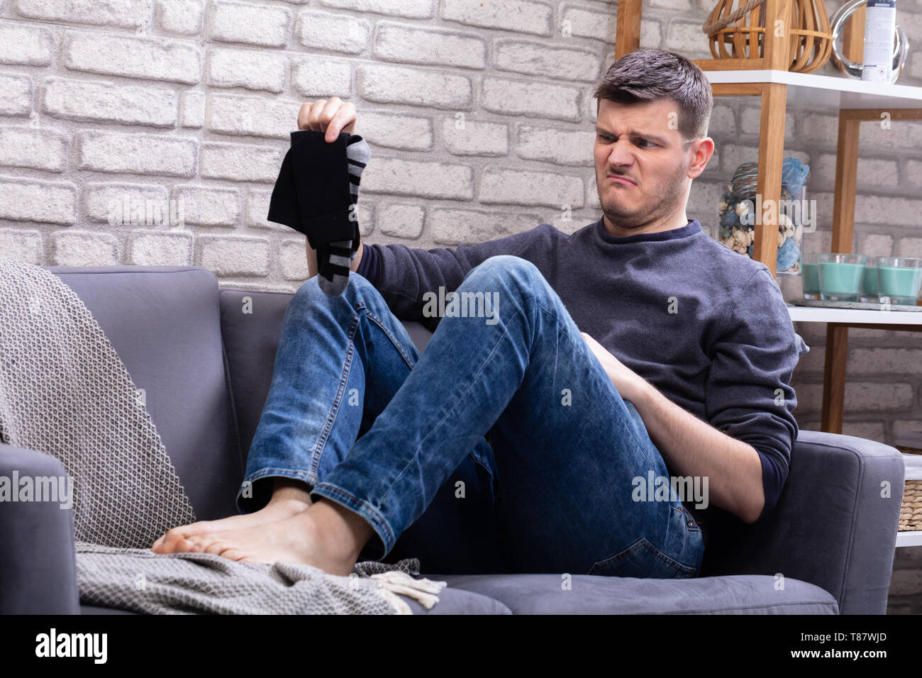 Young Man Sitting On Sofa Holding Dirty Socks - Stock Image