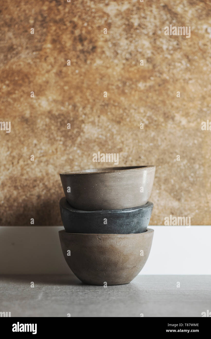 Bowls of polished concrete, handmade, stacked on the kitchen countertop - Stock Image