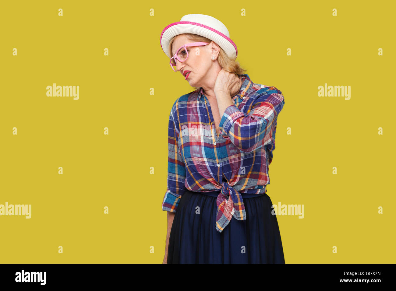 Neck pain. Portrait of sick modern stylish mature woman in casual style with hat and eyeglasses standing and holding her painful neck and feeling bad. - Stock Image
