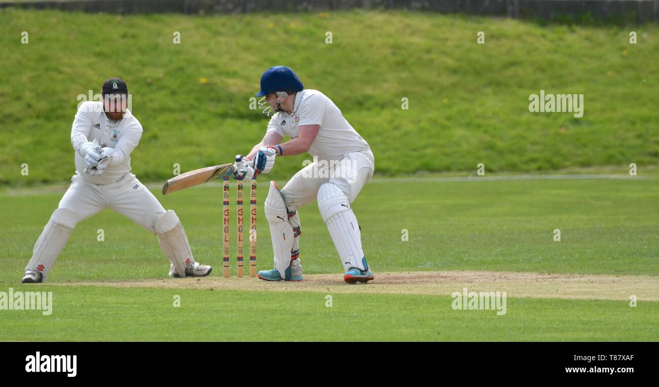 Wicket keeper takes the ball as the batsman is beaten in the match between Glossop and Moorside. - Stock Image