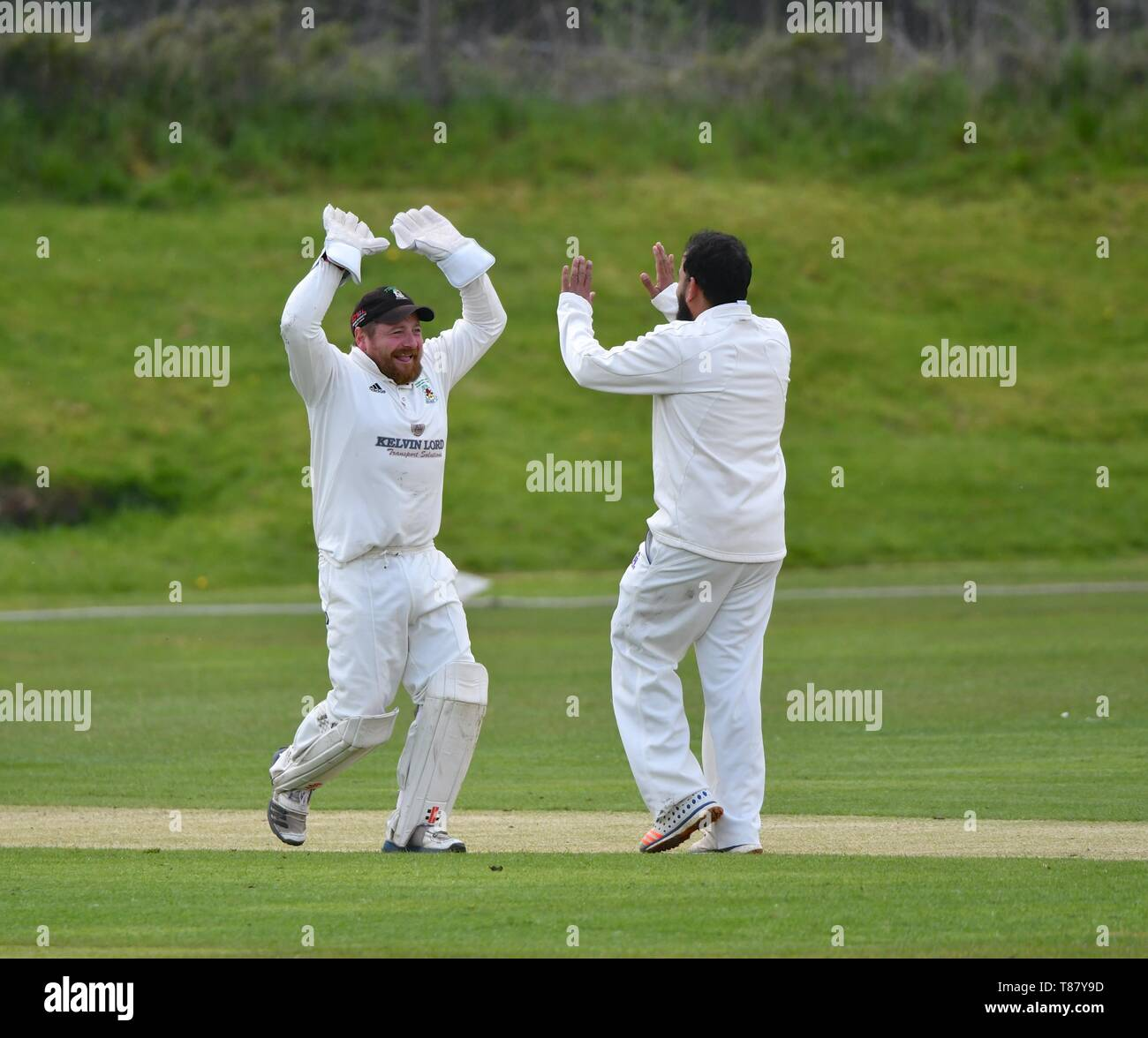 Wicket keeper celebrates a wicket with the bowler  in the match between Glossop and Moorside. - Stock Image