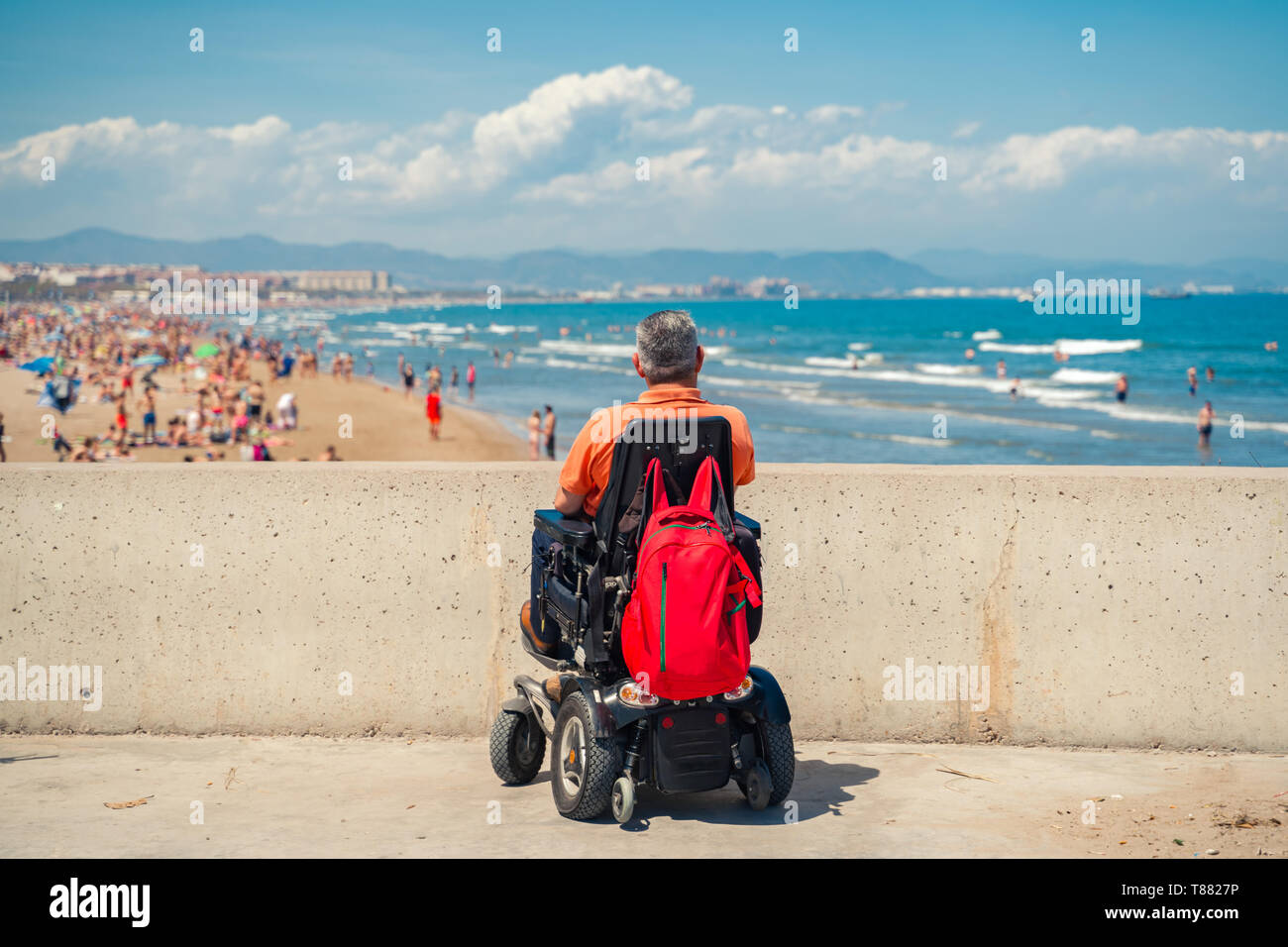 Lonely man on electric wheelchair looking  at the beach. Disabled person at the beach. - Stock Image