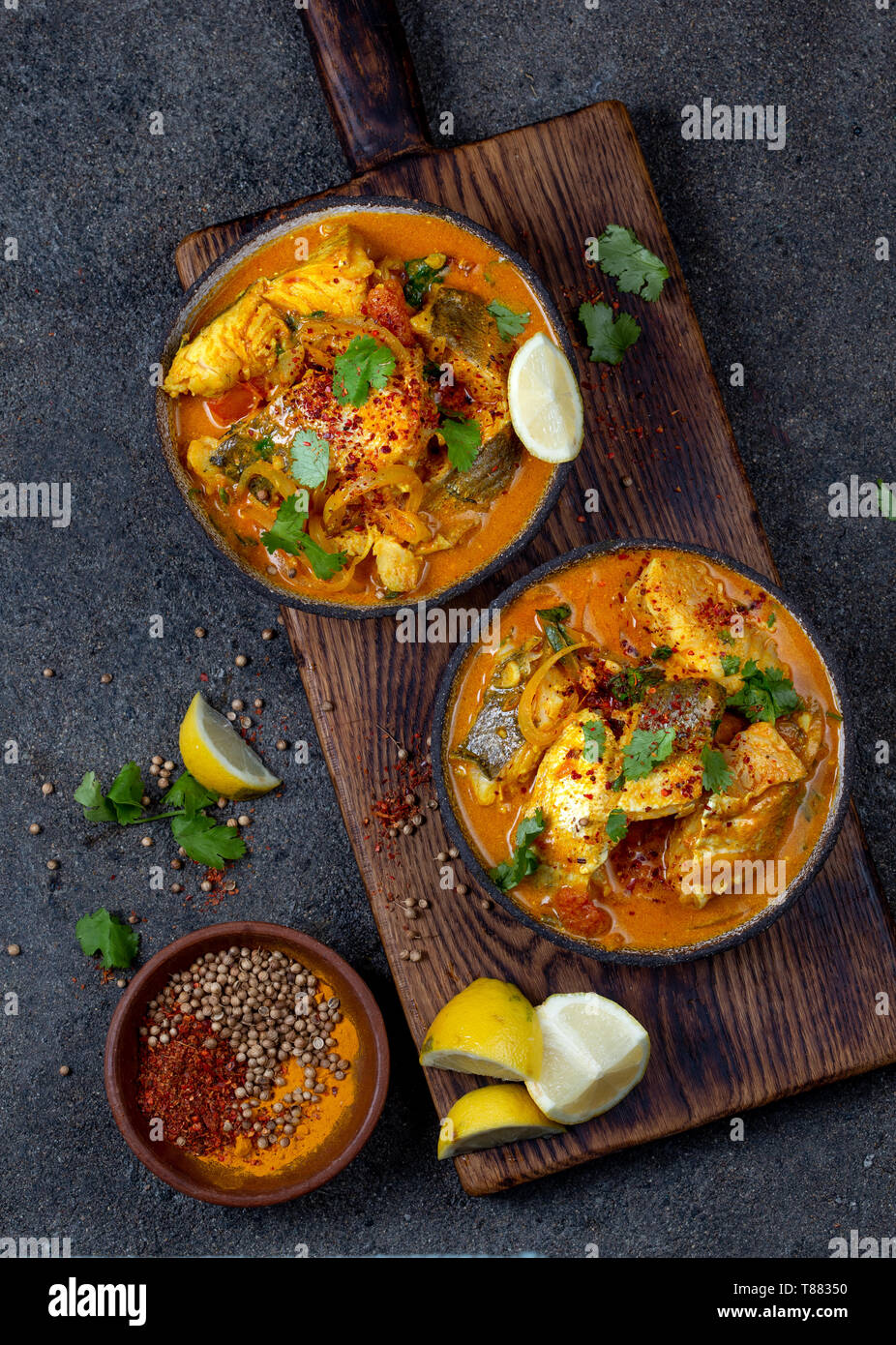 INDIAN FOOD. Traditional KERALA FISH CURRY with naan bread, gray plate, black background  - Stock Image