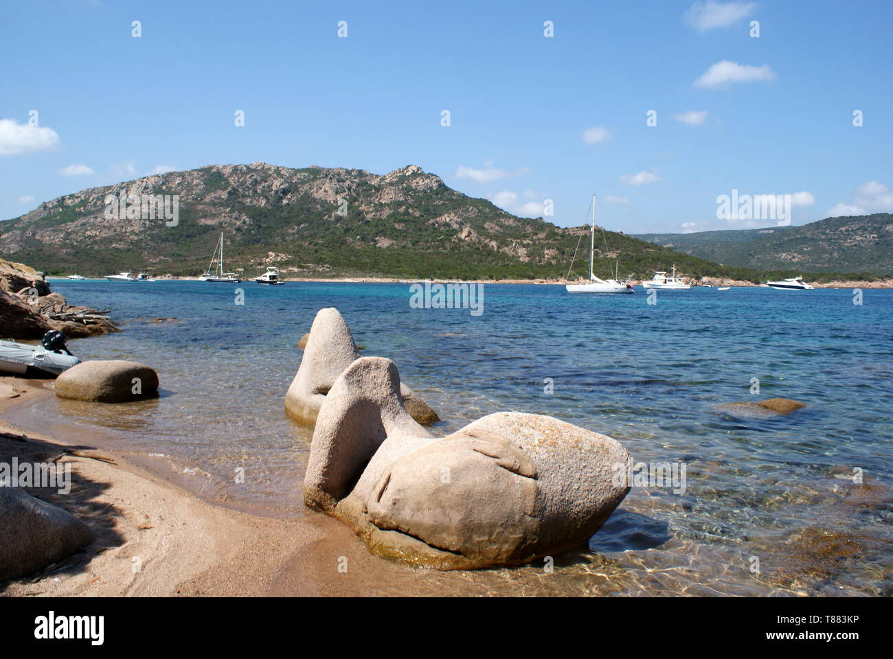 Large rocks on the beach and yachts anchored in the Gulf of Porto Novo, Corsica, France - Stock Image