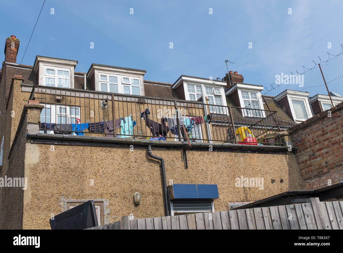 Washing hung out to dry on the rooftop terrace of a flat in city suburbs. - Stock Image
