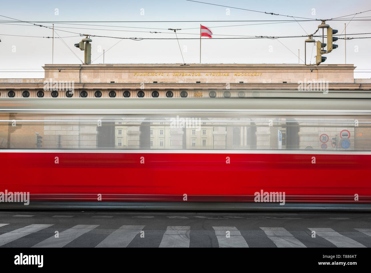 Vienna city transport, view of a tram on the Ringstrasse in Vienna speeding past the (Heldenplatz) entrance to the Hofburg Palace, Austria. Stock Photo