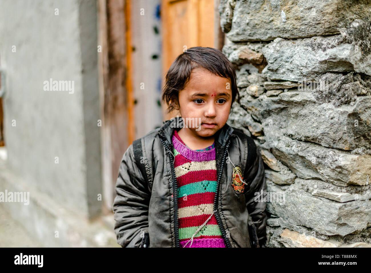 Kullu, Himachal Pradesh, India - April 01, 2019 : Portrait himachali girl near her house on the street in Himalayan village - India - Stock Image
