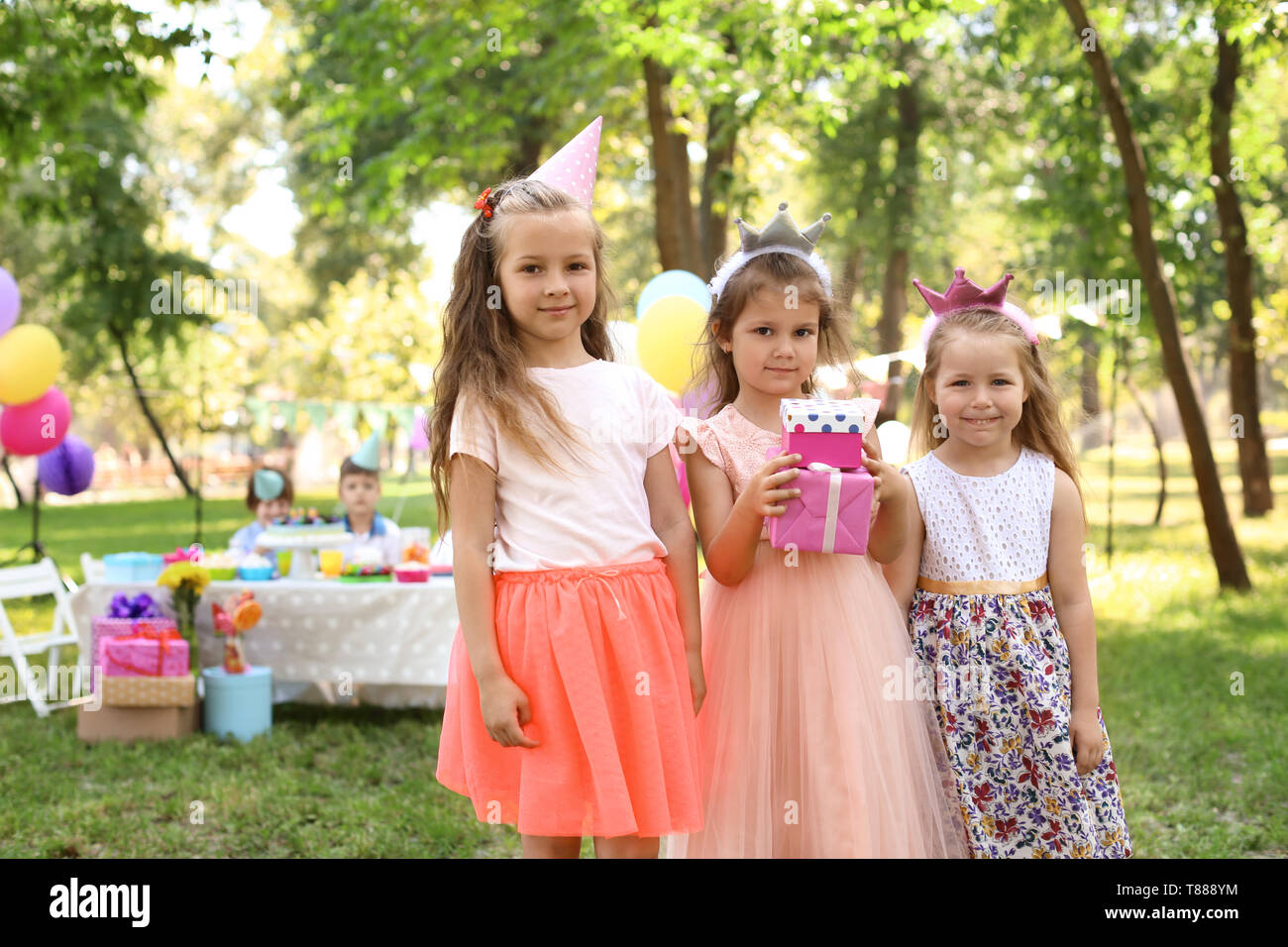 Cute Little Girl With Gift Boxes And Her Friends At Birthday Party
