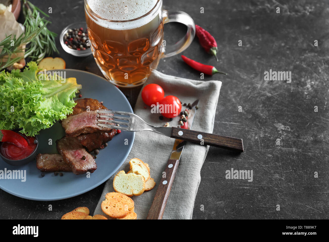 Mug of delicious beer with grilled steak and spices on grey table Stock Photo
