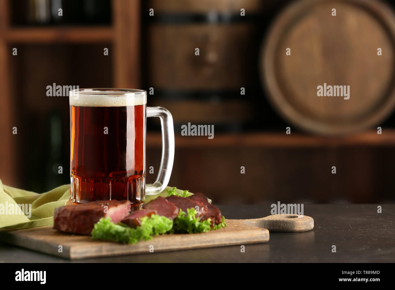 Mug of delicious beer with grilled steak on table Stock Photo