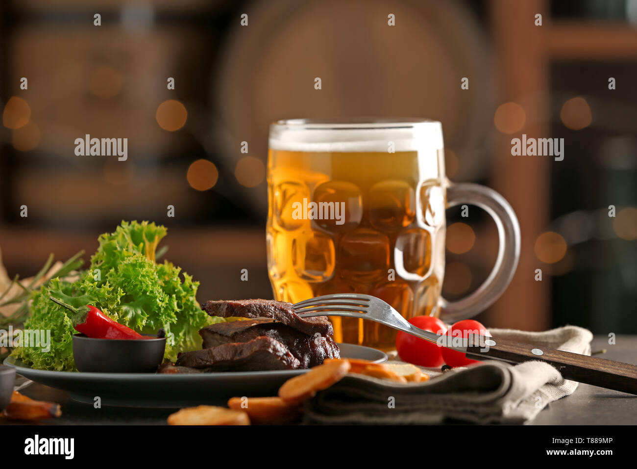 Mug of delicious beer with grilled steak and sauce on table Stock Photo