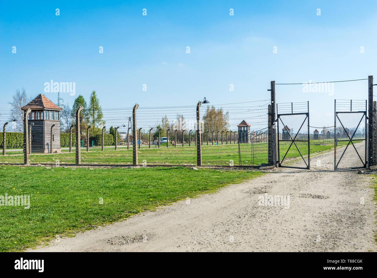 AUSCHWITZ (OSWIECIM), POLAND - APRIL 18, 2019: Electric fence and barracks in Auschwitz Birkenau extermination death camp, Poland - Stock Image