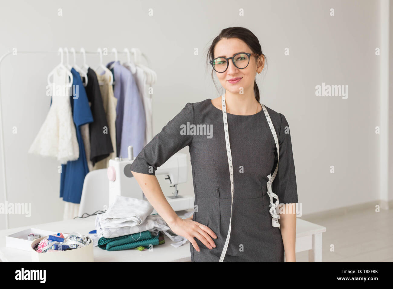 Dressmaker Fashion Designer And Tailor Concept Young Dressmaker Woman Over Clothes Rack With Dresses Background Stock Photo Alamy