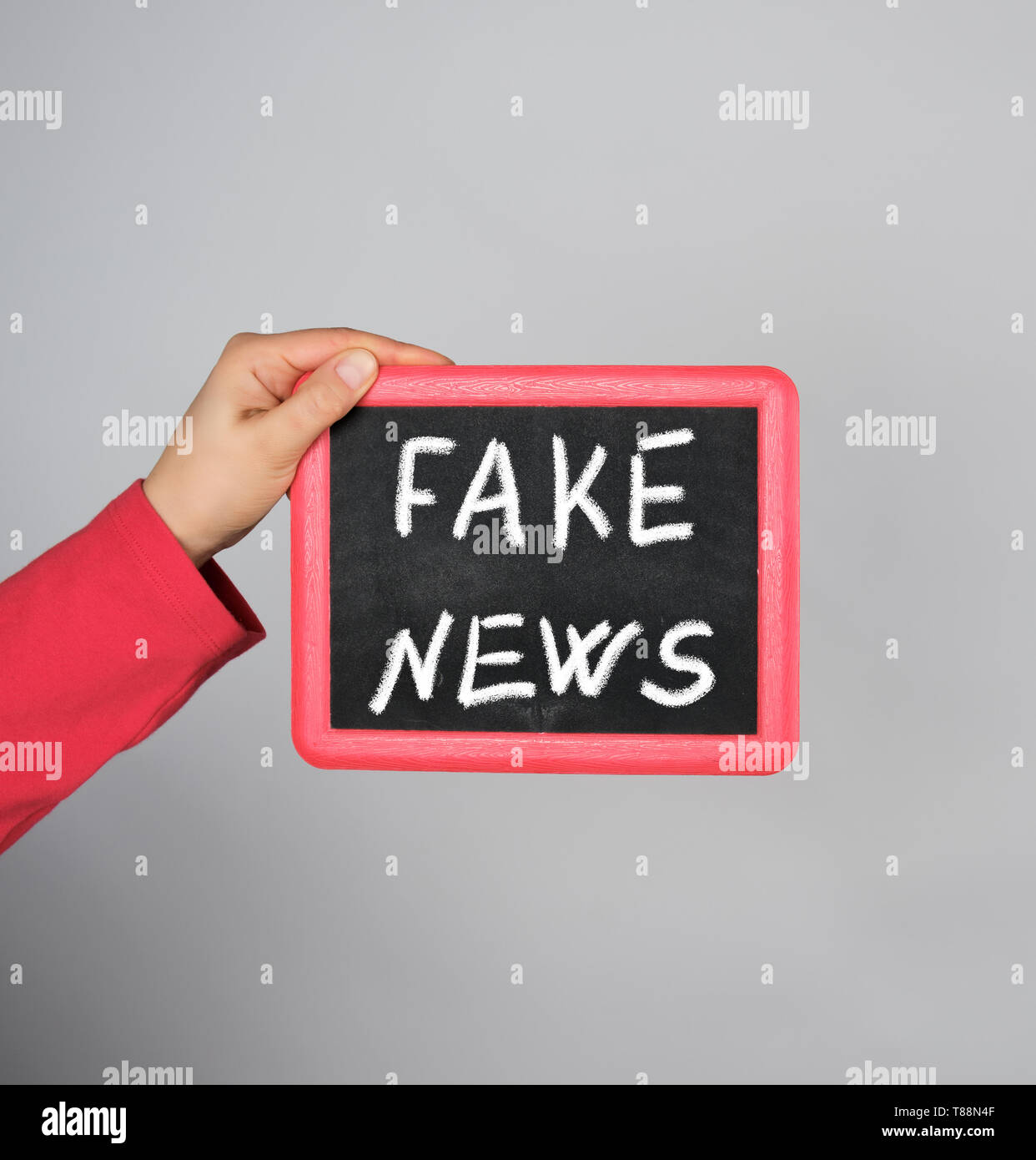 female hand holding red frame with chalk inscription fake news on gray background Stock Photo
