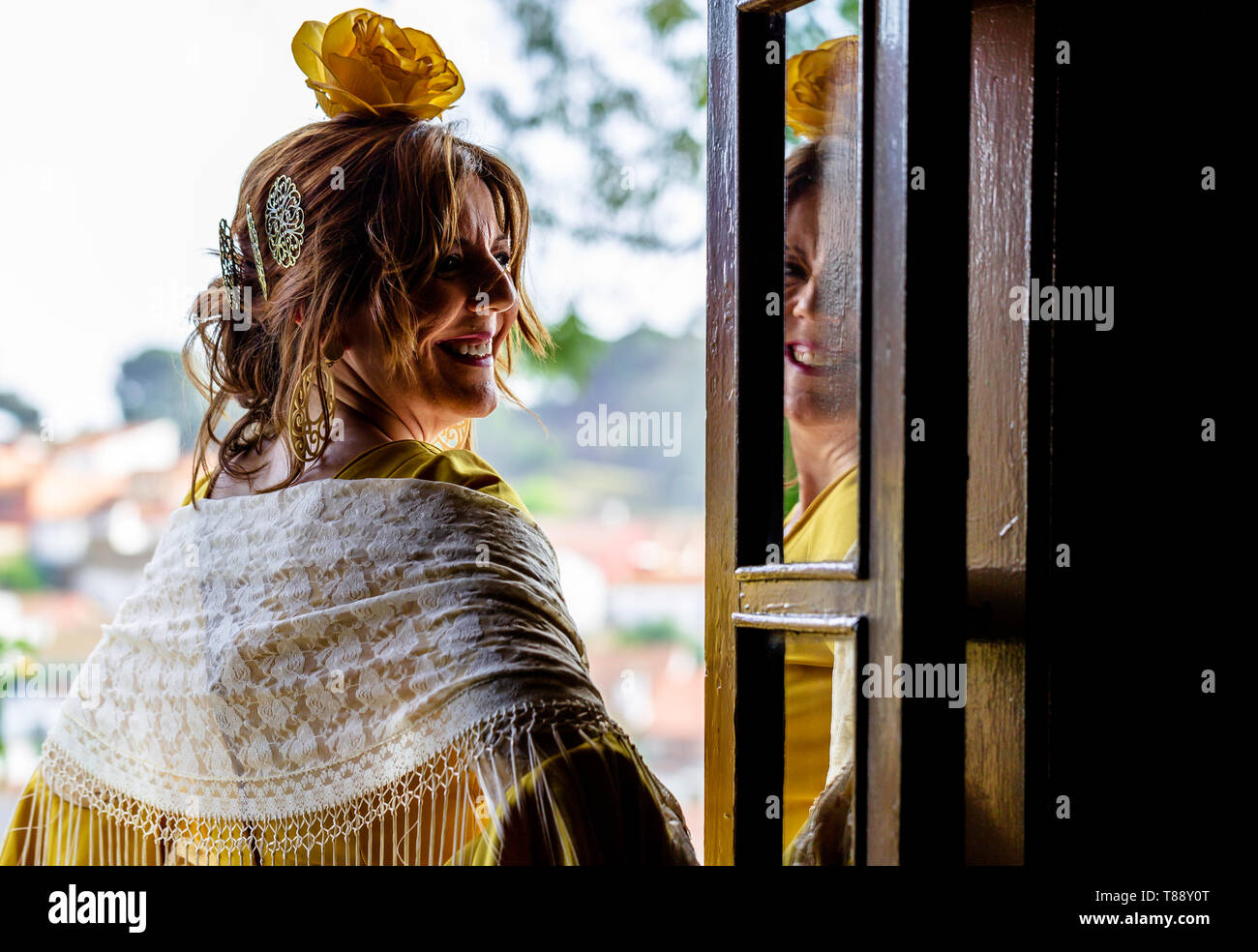 A Spanish woman wearing a bright yellow traditional flamenco style dress in Andalusia standing in front of a door and reflecting the face in the glass - Stock Image