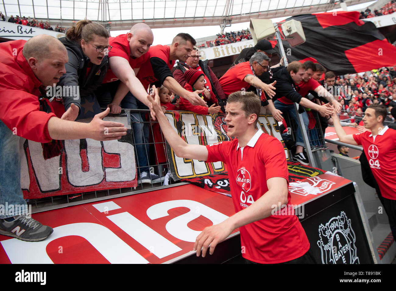 Leverkusen, Germany. 11th May, 2019. Soccer: Bundesliga, Bayer Leverkusen - FC Schalke 04, 33rd matchday in the BayArena. Leverkusen's Sven Bender (M) claps his hands with the fans in the stands. Credit: Federico Gambarini/dpa - IMPORTANT NOTE: In accordance with the requirements of the DFL Deutsche Fußball Liga or the DFB Deutscher Fußball-Bund, it is prohibited to use or have used photographs taken in the stadium and/or the match in the form of sequence images and/or video-like photo sequences./dpa/Alamy Live News - Stock Image