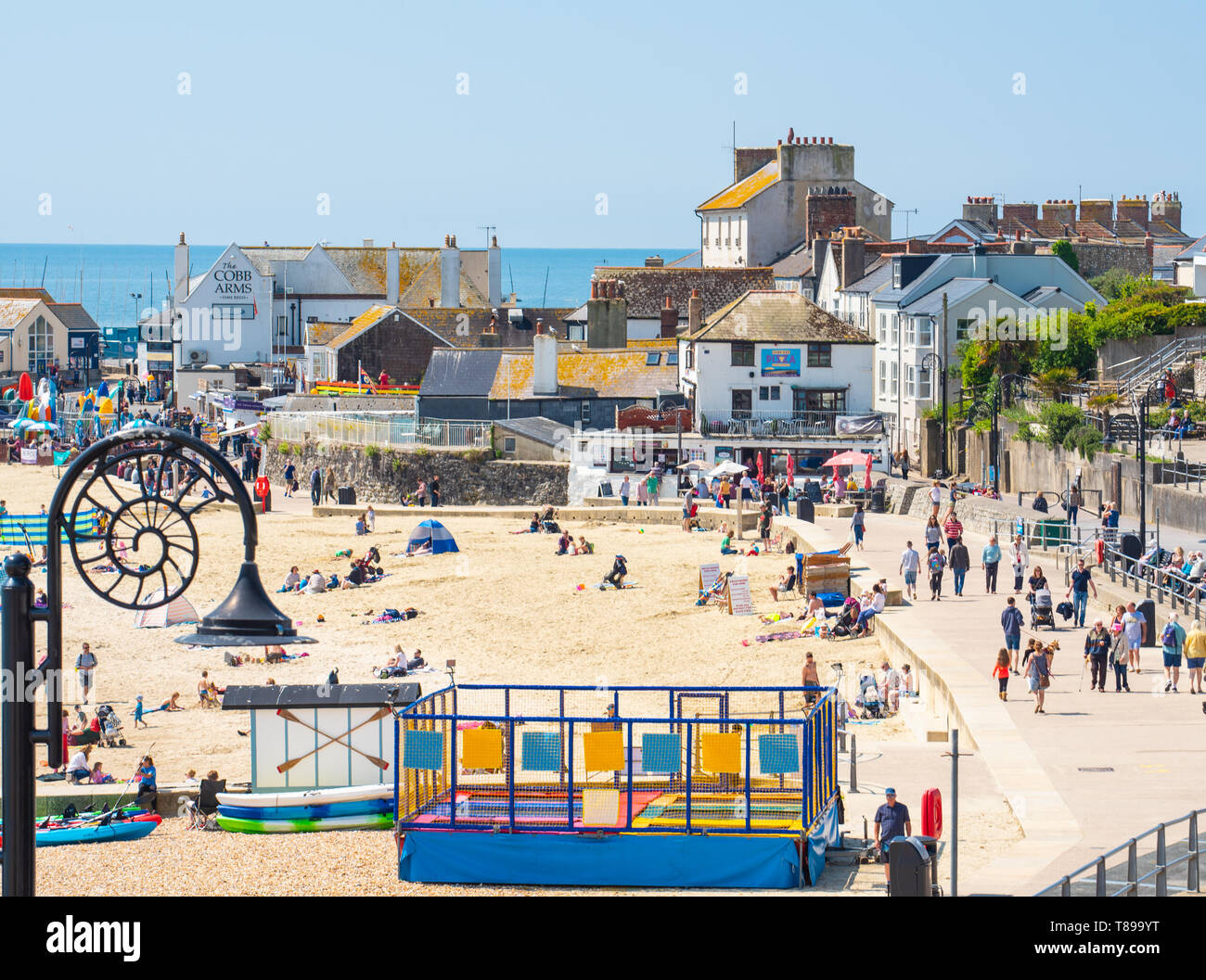 Lyme Regis, Dorset, UK. 12th May 2019. UK Weather: Visitors and beach goers enjoy the picturesque beach at the seaside resort of Lyme Regis on a hot and sunny Sunday.  Temperatures are set to soar with highs of 25 degrees celsius forecast for the coming week. Credit: Celia McMahon/Alamy Live News. - Stock Image