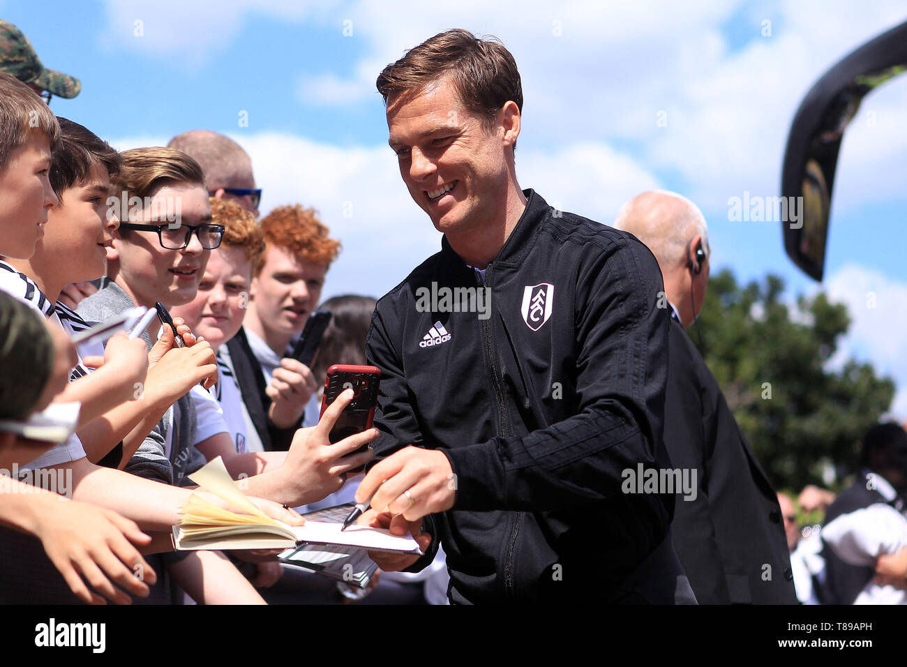 London, UK. 12th May, 2019. Fulham Manager Scott Parker signs autographs for fans outside the ground. Premier League match, Fulham v Newcastle Utd at Craven Cottage in London on Sunday 12th May 2019.  this image may only be used for Editorial purposes. Editorial use only, license required for commercial use. No use in betting, games or a single club/league/player publications. Credit: Andrew Orchard sports photography/Alamy Live News - Stock Image