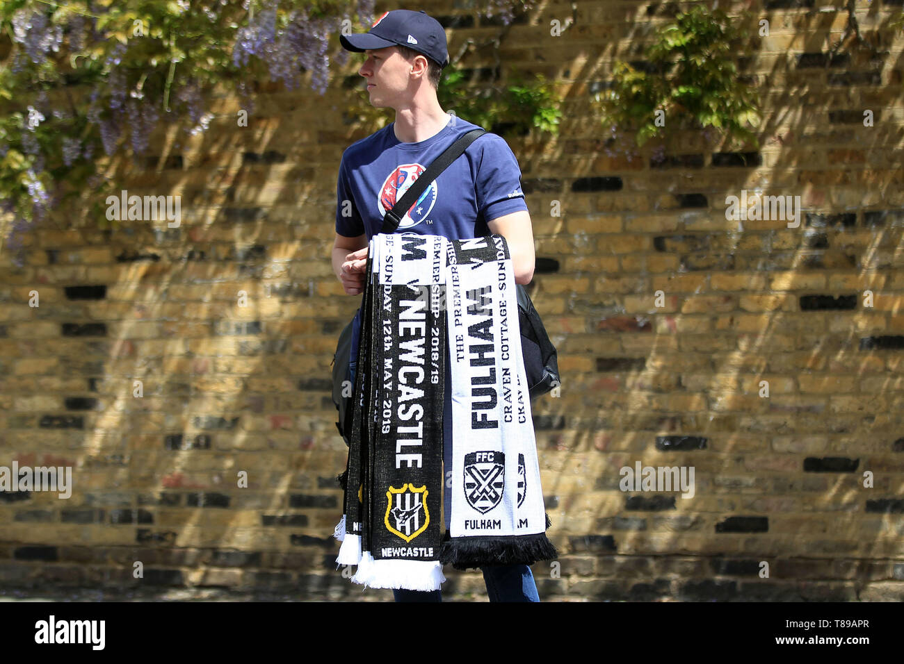 London, UK. 12th May, 2019. A merchandise seller sells scarves outside the ground. Premier League match, Fulham v Newcastle Utd at Craven Cottage in London on Sunday 12th May 2019.  this image may only be used for Editorial purposes. Editorial use only, license required for commercial use. No use in betting, games or a single club/league/player publications. Credit: Andrew Orchard sports photography/Alamy Live News - Stock Image