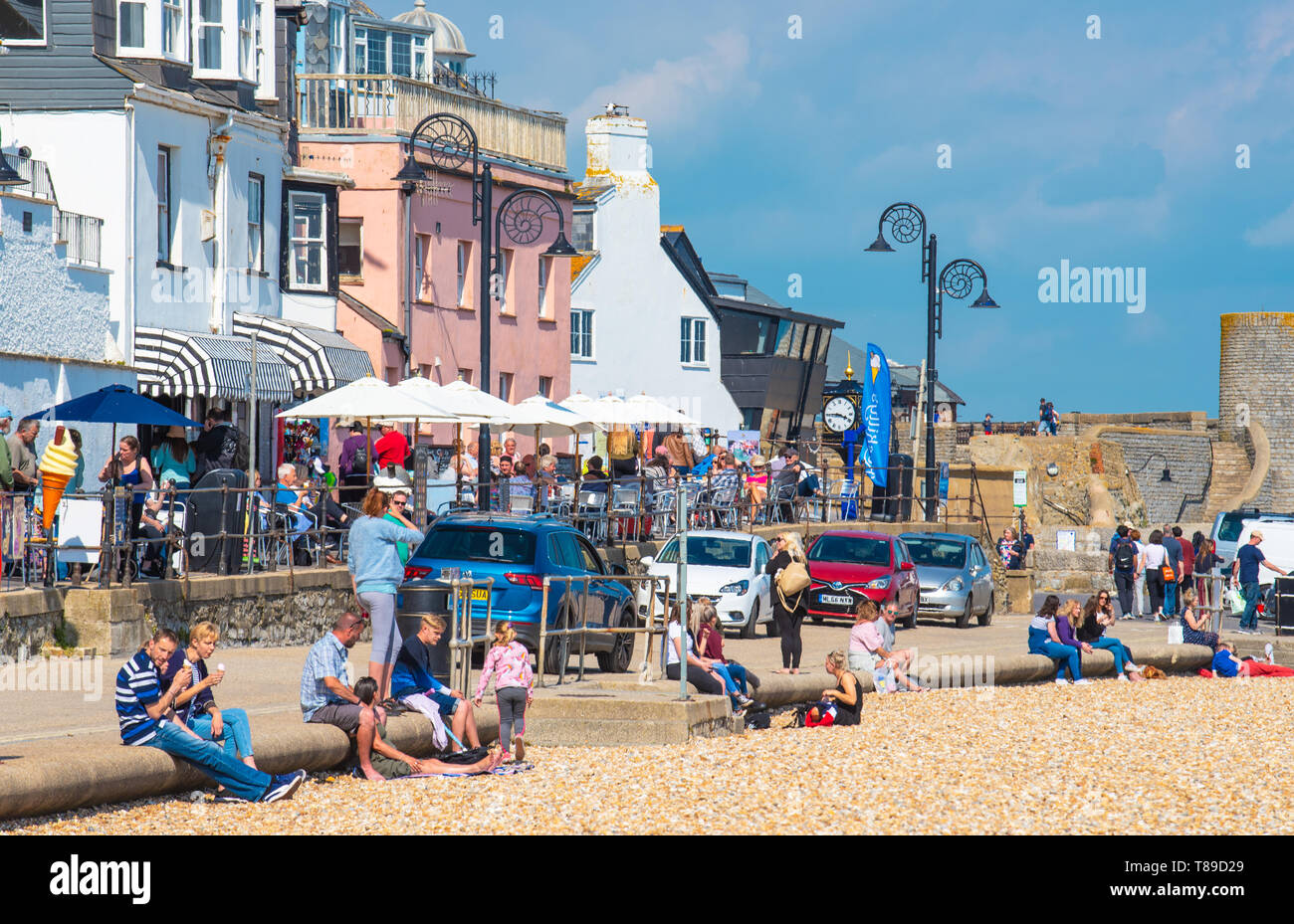 Lyme Regis, Dorset, UK. 12th May 2019. UK Weather: The beach at Lyme Regis was unseasonably busy on Sunday afternoon as visitors enjoyed the hot sunshine and blue sky.  Temperatures are set to soar with highs of 25 degrees celsius forecast for the coming week. Credit: Celia McMahon/Alamy Live News. - Stock Image