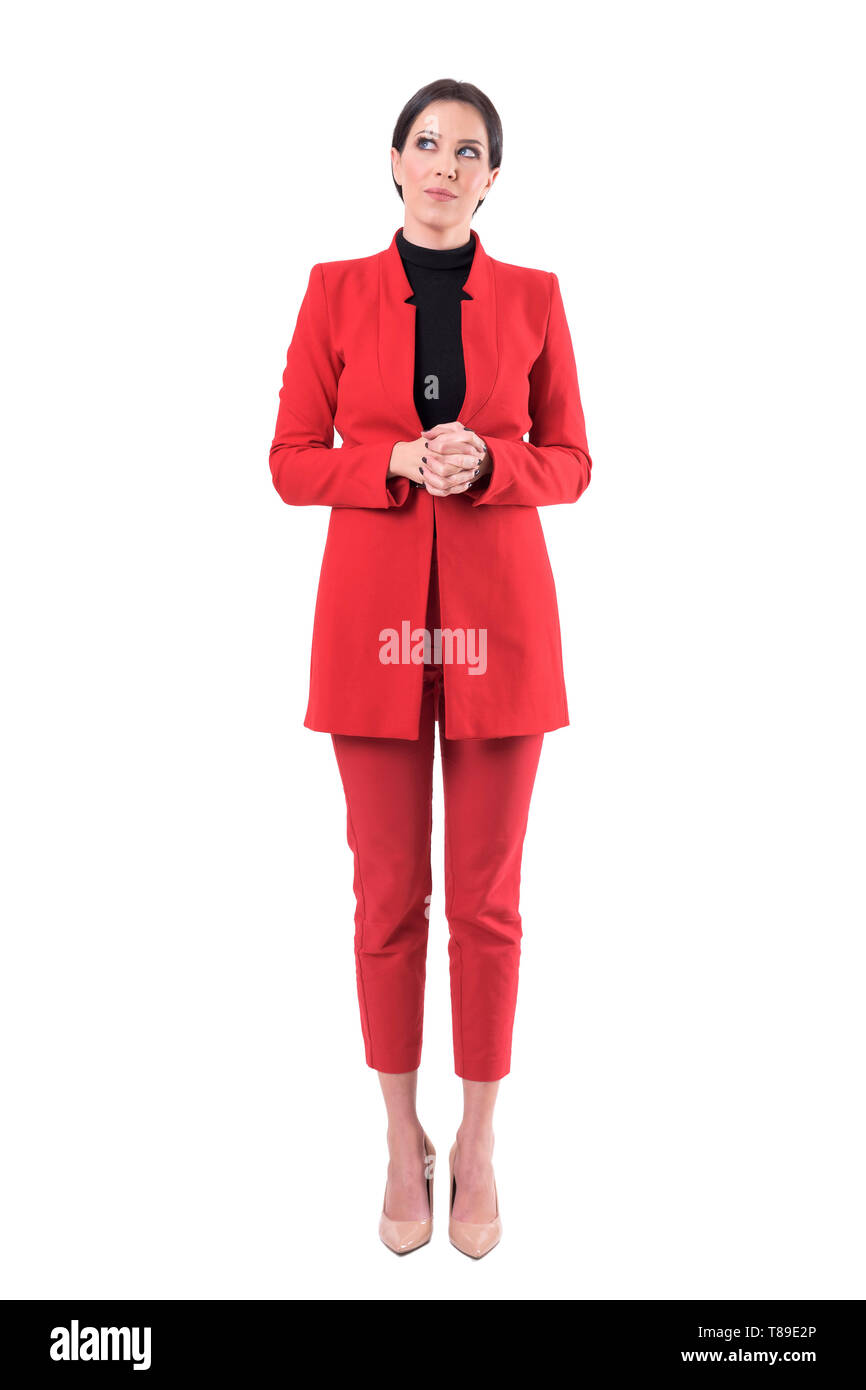 Elegant young business woman in red suit looking up thinking and having idea. Full body isolated on white background. - Stock Image