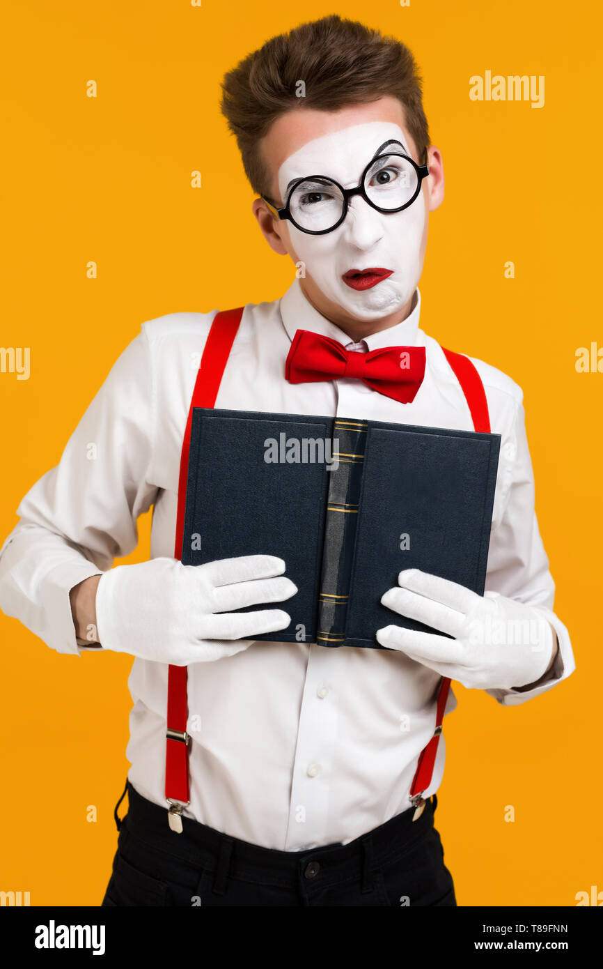 portrait of mime man artist with book ape isolated on yellow background - Stock Image