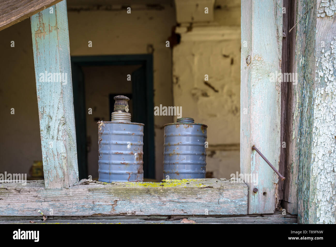 Two metal cans behind a window with broken glass of an old abandoned house in Belarus Chernobyl exclusion zone in Belarus - Stock Image