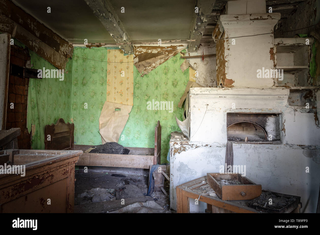 Interior with furnace and bed in an abandoned little house in Belarus Chernobyl exclusion zone, recently opened for the public from april 2019. - Stock Image