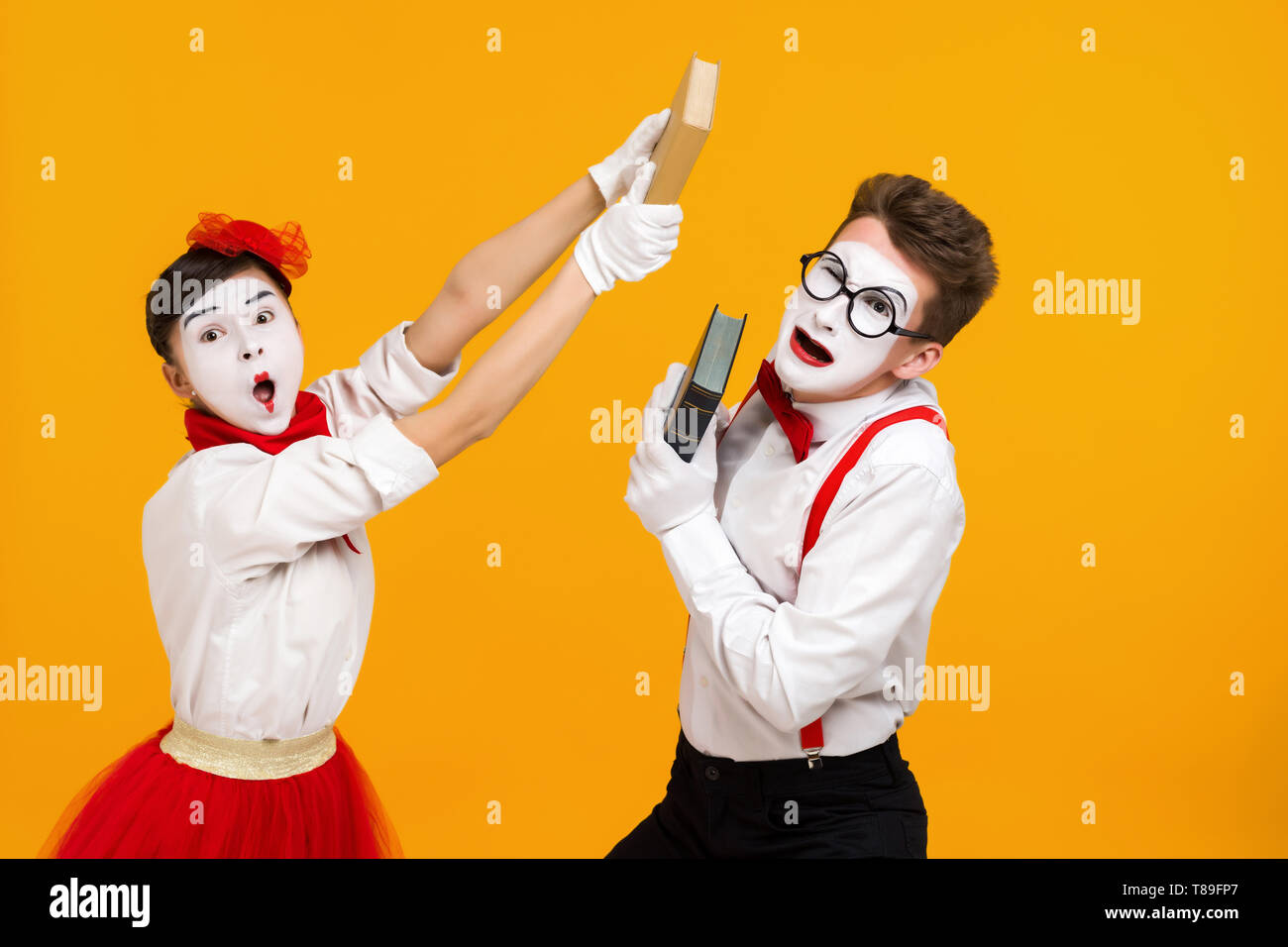 portrait of mime couple artist quarreling and reading book isolated on yellow background - Stock Image