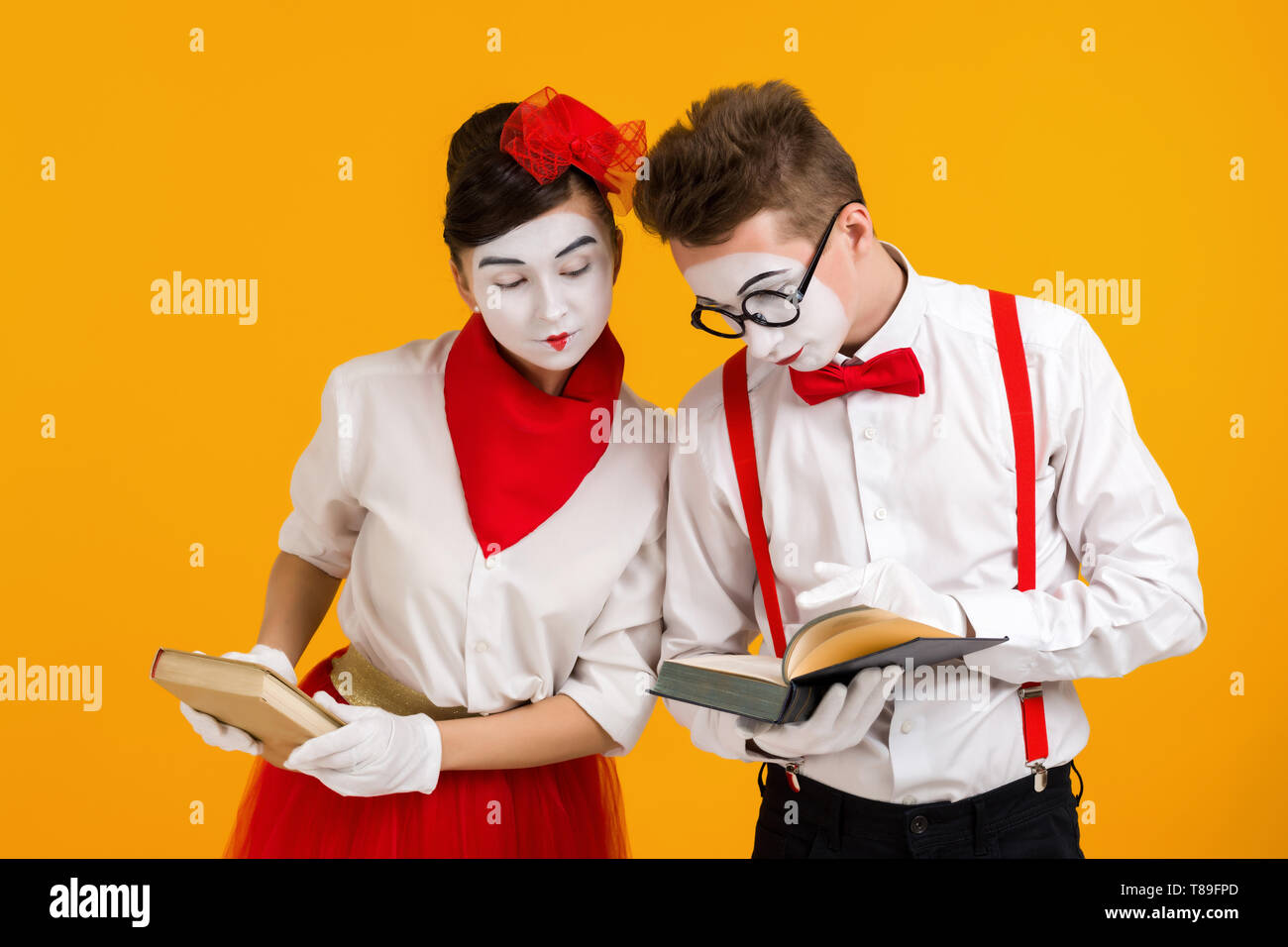 portrait of mime couple artist reading book isolated on yellow background - Stock Image