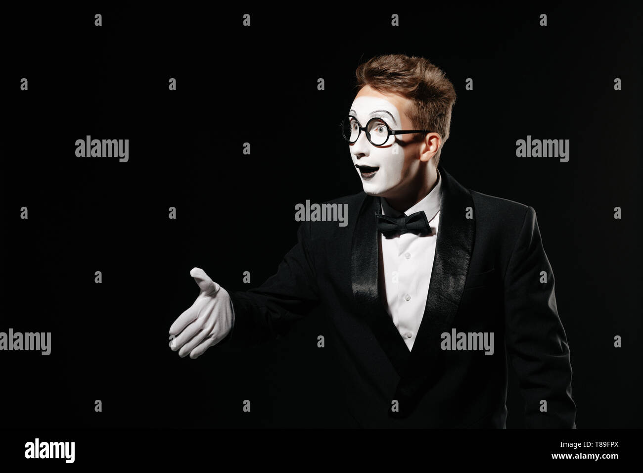 portrait of mime man in tuxedo and glasses giving hand for handshake on black background - Stock Image