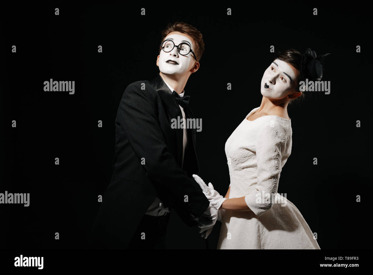 portrait of couple mime on black background. man in tuxedo and glasses and woman in white dress - Stock Image