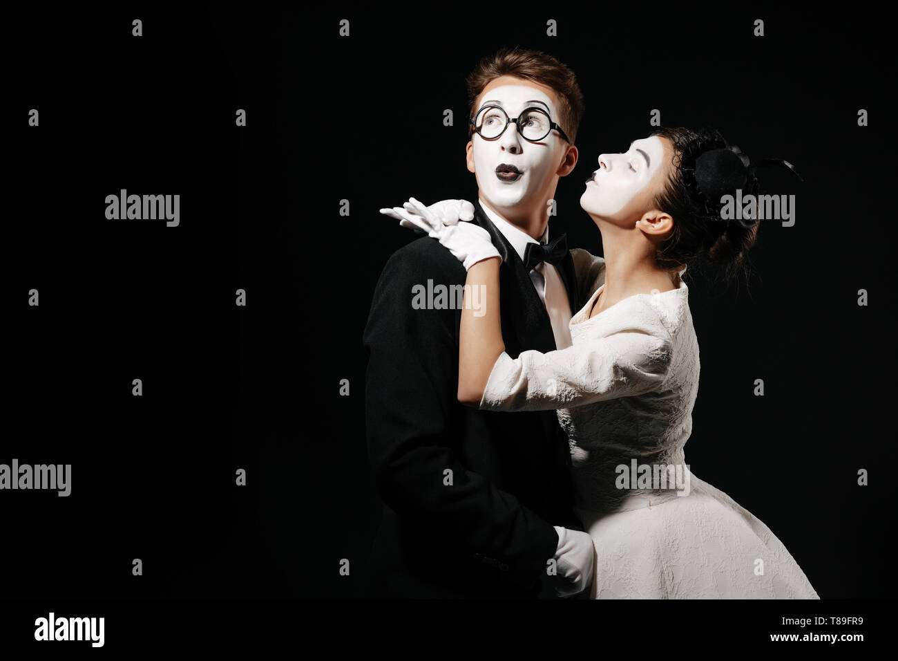 portrait of couple mime on black background. woman in white dress kissing man in tuxedo and glasses - Stock Image