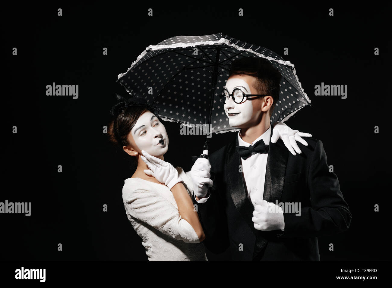 portrait of couple mime with umbrella on black background. man in tuxedo and glasses and woman in white dress - Stock Image