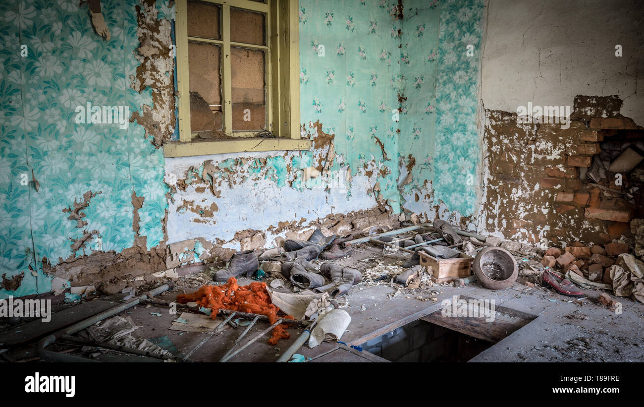 Old shoes in an abandoned little house in Belarus Chernobyl exclusion zone, recently opened for the public from april 2019. - Stock Image