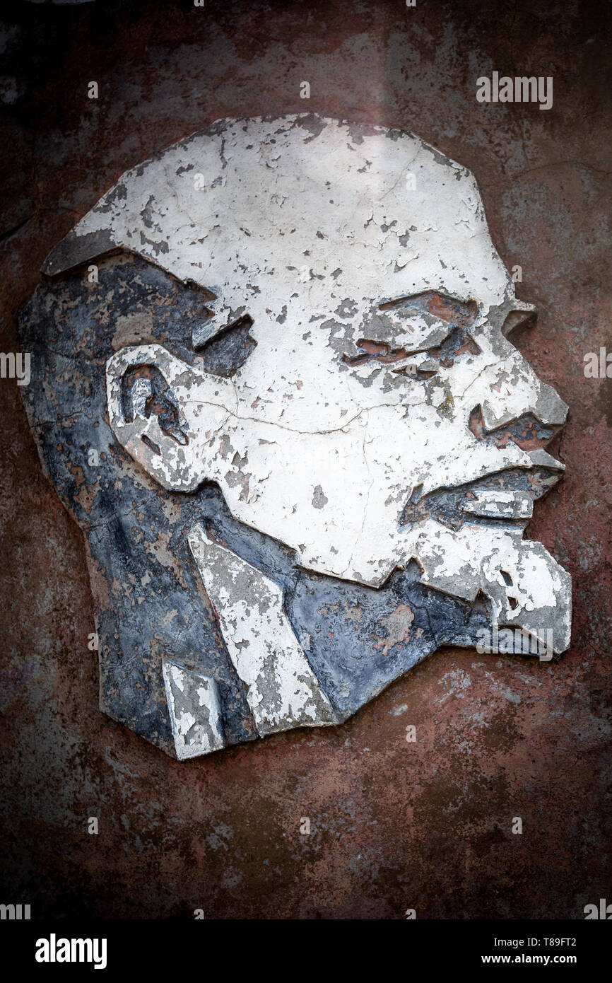 Weathered sculpture of  Lenin on a wall n Belarus Chernobyl exclusion zone. - Stock Image