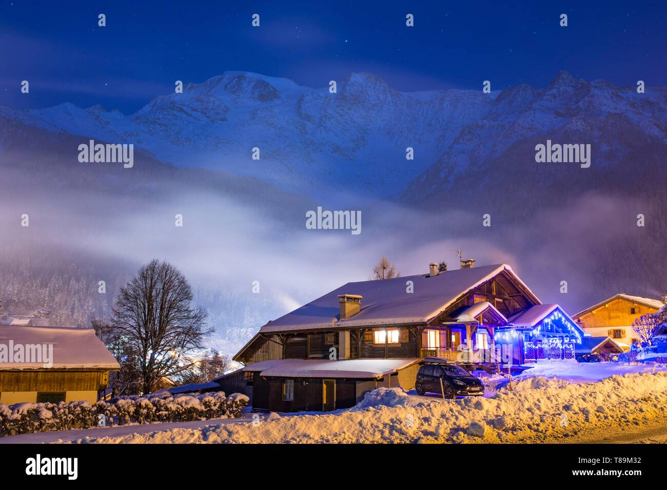 France, Haute Savoie, Massif of the Mont Blanc, the Contamines Montjoie, twilight on a chalet lit of the station and the domes of Miage - Stock Image