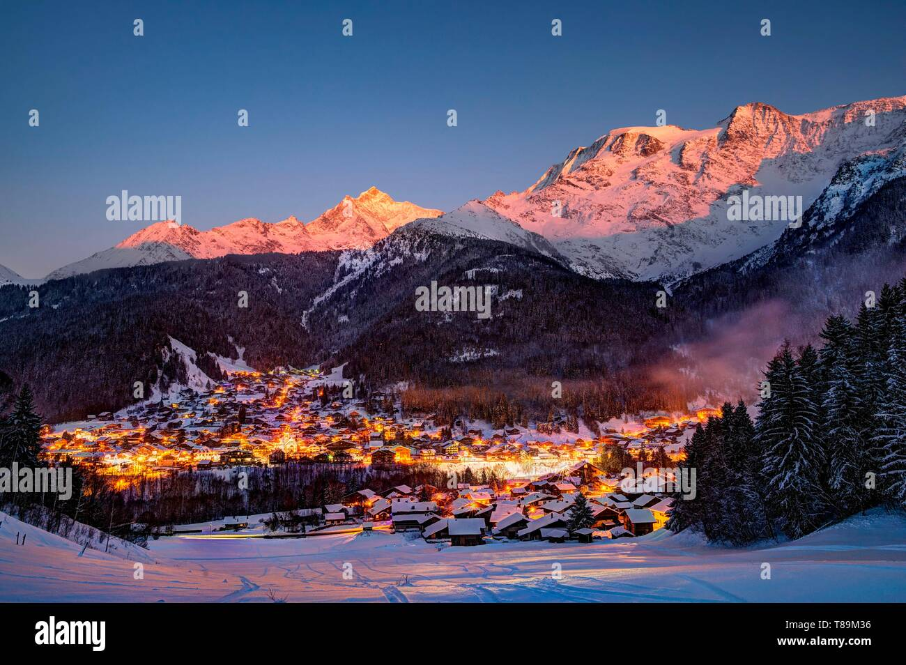 France, Haute Savoie, Massif of the Mont Blanc, the Contamines Montjoie, the overview of the village station(resort) in the twilight and sunset on the needle of Bionnassay and the domes of Miage - Stock Image