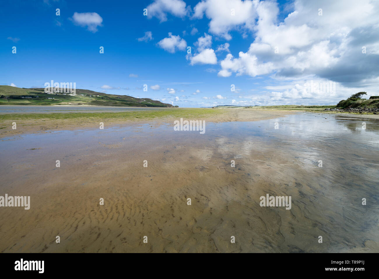 Dunfanaghy Bay at low tide in Donegal, Ireland. White sand and blue sky with clouds at Dunfanaghy beach, a typical irish beach on the northern coast - Stock Image
