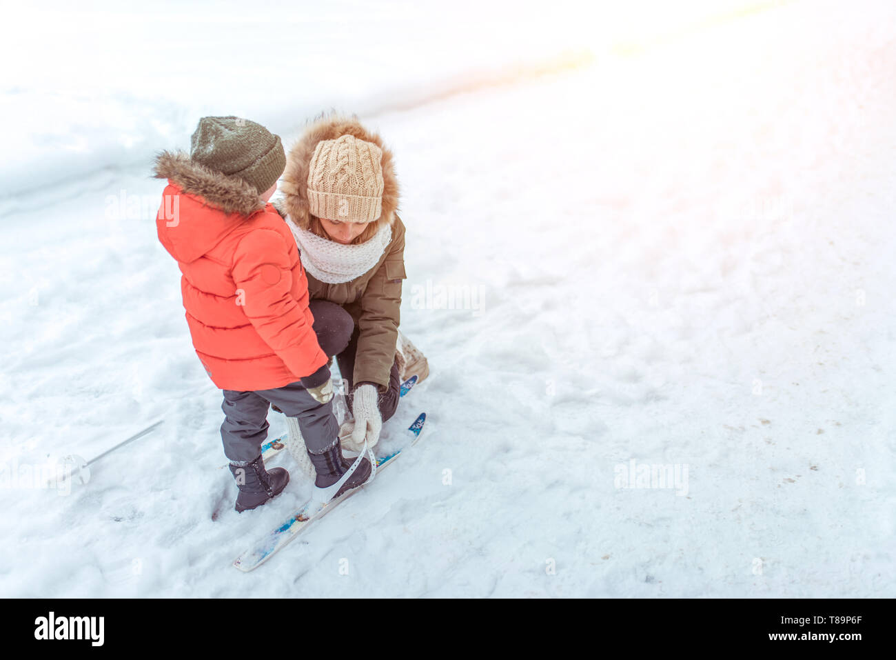 A young mother a woman straightens her skis, a little son, a boy of 3 years. Winter on street in park, background snow drifts road. Free space - Stock Image