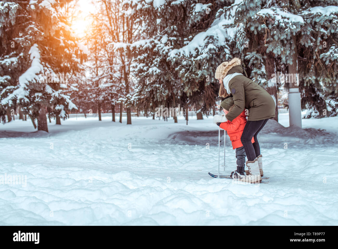 A young mother supports a young son, a boy of 3 years. In winter, outside in park, background is snow drifts of Christmas tree. Free space. Children's Stock Photo