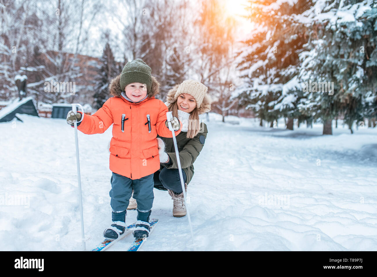 Young mother woman happy smiling, son boy 3 years old laughs. In winter, outside park, background is snow drifts Christmas tree. Free space. Children - Stock Image