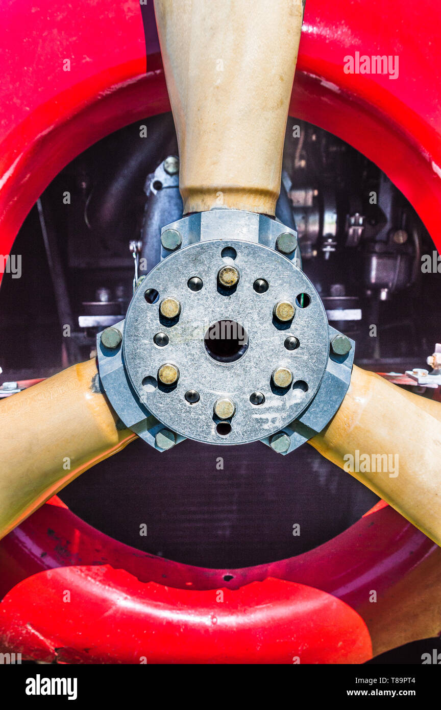 Close front view detail of vintage red biplane propeller, engine, mounting flange and bolts. - Stock Image