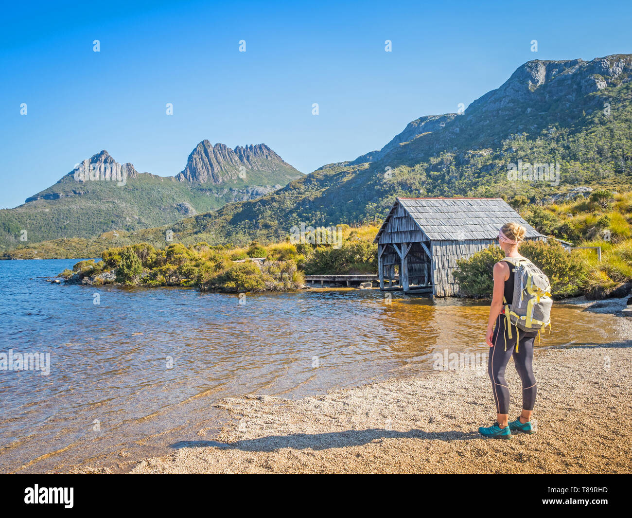 An unidentified female hiker looks at the boathouse at Dove Lake in the Cradle Mountain - Lake St Clair National Park in Tasmania. Stock Photo