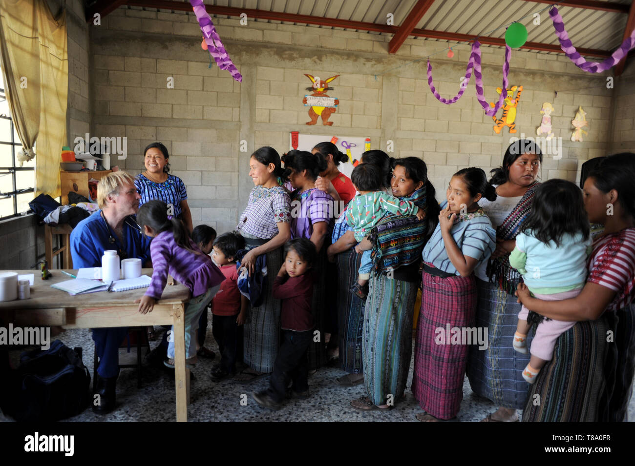 Maya indigenous mothers and children at clinic provided by local NPO in Chuk Muk, Solola, Guatemala. - Stock Image