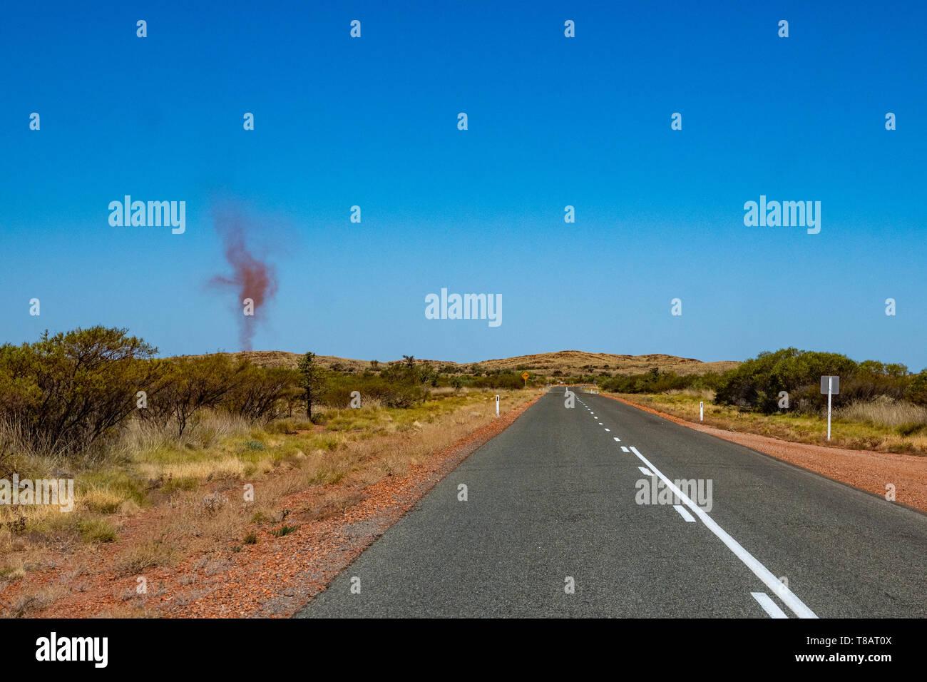 Dust devil besides dark road leading through red sanded Australian landscape towards Karijini National Park - Stock Image