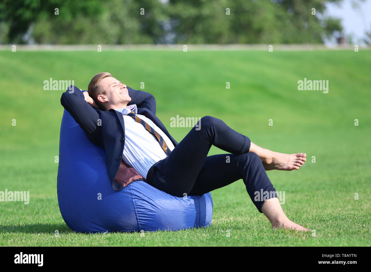 Young man in formal clothes relaxing on green grass outdoors - Stock Image