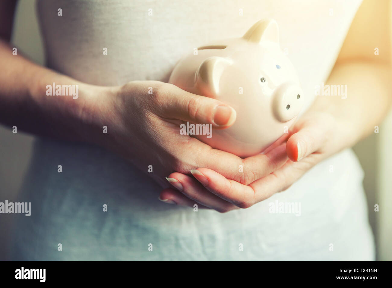 Female woman hands holding pink piggy bank. Saving investment budget business wealth retirement financial money banking concept - Stock Image